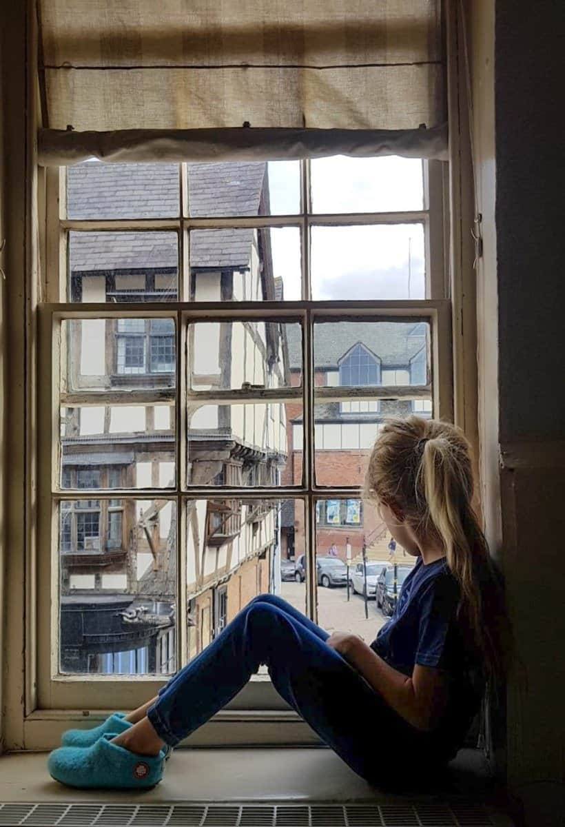 girl sitting on the window sill and looking at the street