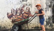 girl standing at the mural with orangutans in Kuching, things to do in kuching with kids